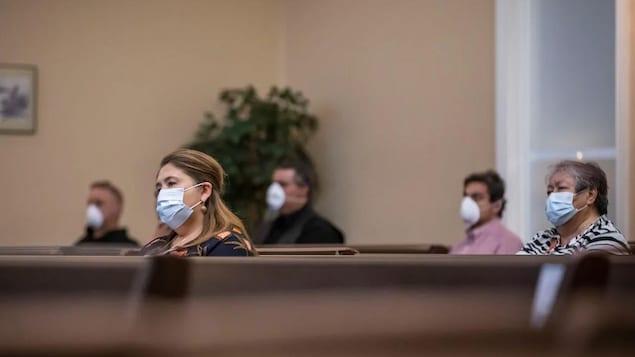 Un groupe de personnes portant un masque assistent à une célébration religieuse.
