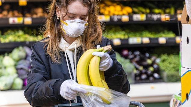 Une femme portant un masque et des gants place des bananes dans un sac en plastique.