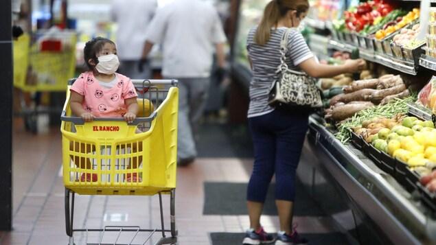 Une petite fille et sa mère portent des masques en faisant l'épicerie.