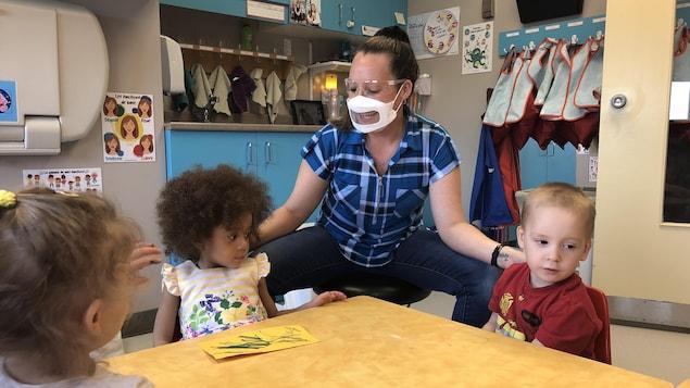 Une éducatrice porte un masque avec une fenêtre. Elle parle aux trois enfants assis avec elle.