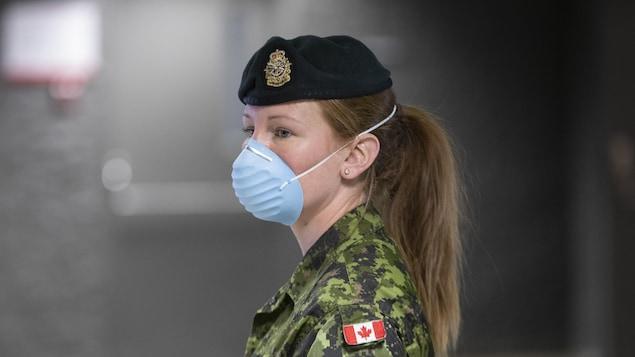 Une militaire avec un masque.