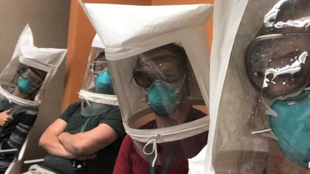 Quatre hommes sont assis sur des chaises dans un hôpital avec d'énormes masques blancs qui protège leur tête au complet.