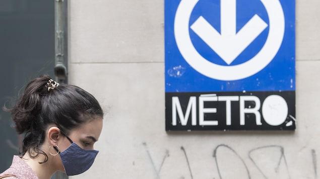 Une femme porte un masque devant une affiche du métro.