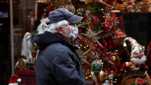 Un homme le visage couvert d'un masque passe devant la vitrine d'un magasin décorée d'un sapin de Noël, le 11 novembre 2020 à Budapest, en Hongrie.