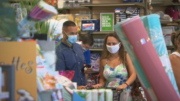 Deux personnes portent le masque dans un commerce.