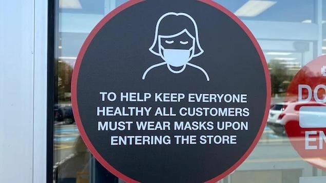 Une autocollant sur une porte de magasin indique que le port du masque est obligatoire.