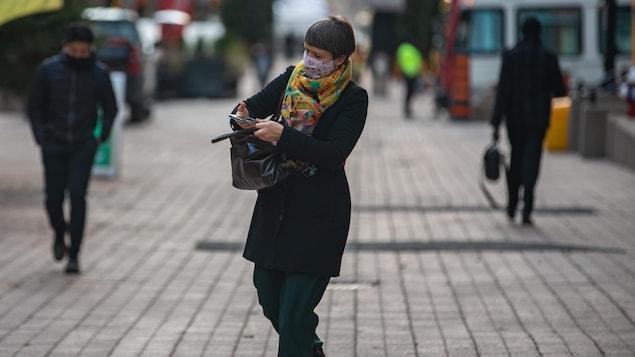 Une femme masquée, marche en consultant son téléphone cellulaire.