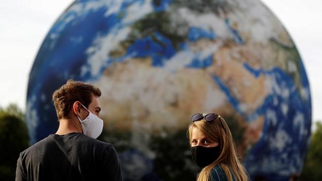Un homme et une femme devant une Terre géante gonflable.