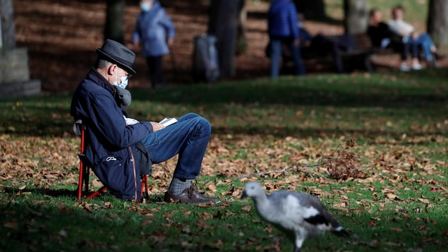 À Nantes, en France, le 9 novembre 2020, un homme âgé est assis au milieu d'un parc sur une très petite chaise pliante, lisant un livre posé sur ses genoux.
