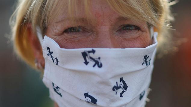Une femme aux cheveux blonds courts a sur son nez et sa bouche un masque en tissu blanc avec des motifs d'ancres de bateau.