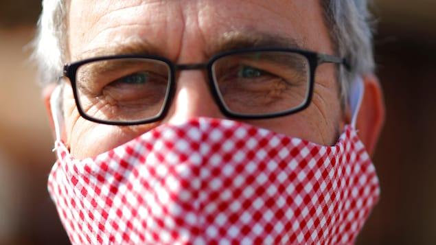 Un homme aux cheveux gris porte des lunettes carrées à monture noire. Son nez et sa bouche sont recouverts d'un masque en tissu blanc à carreaux rouges.