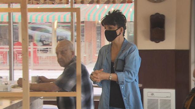 Une dame entre dans un restaurant en portant son masque.