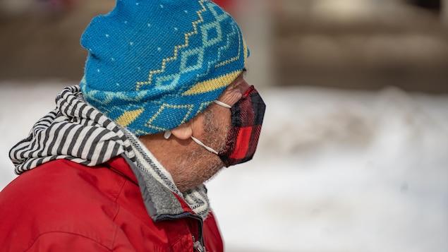 Un homme qui marche dans la rue porte un masque à carreaux rouge et noir et une tuque.