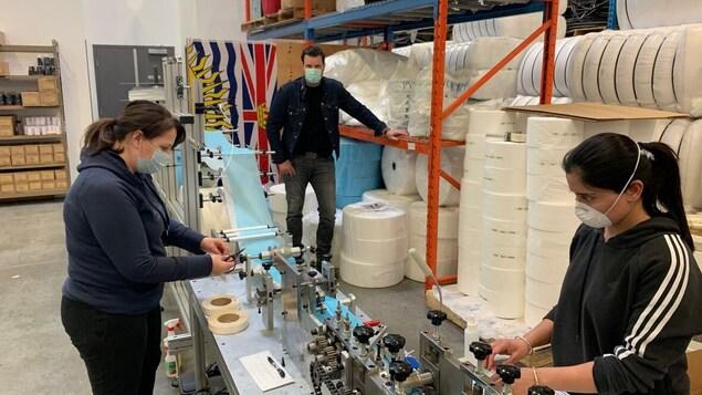 Des employés travaillent à la production de masques chirurgicaux dans une usine du Grand Vancouver.
