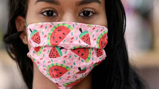 Une femme porte un masque à motif de melons d'eau.