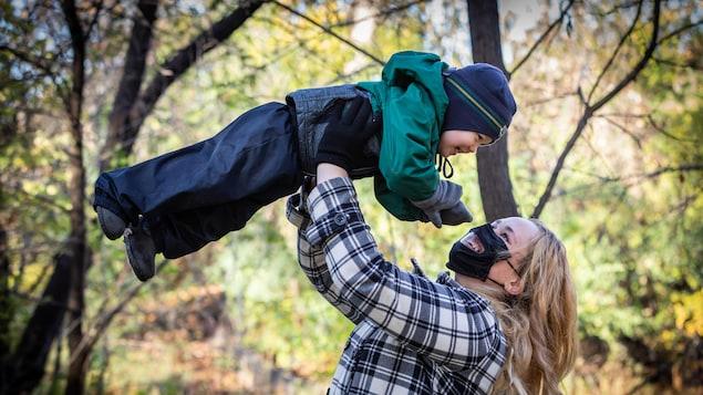 Une femme qui porte un masque avec une fenêtre soulève un enfant.