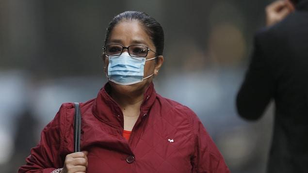 Une femme portant un masque dans la rue.