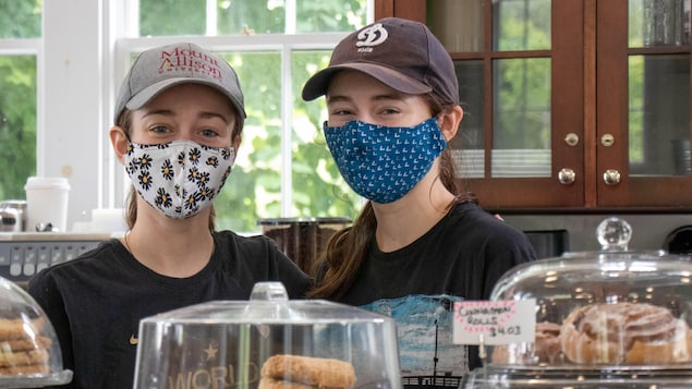 Deux jeunes femmes coiffées de casquette et le visage couvert d'un masque de tissu sont debout derrière le comptoir du café où elles travaillent.