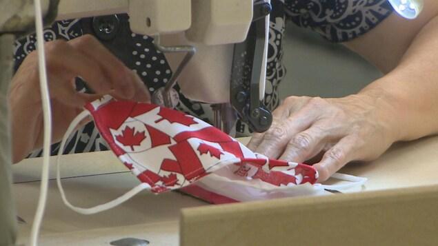 Un gros plan sur l'aiguille de la machine à coudre d'une femme qui effectue la finition d'un masque aux couleurs du drapeau canadien.