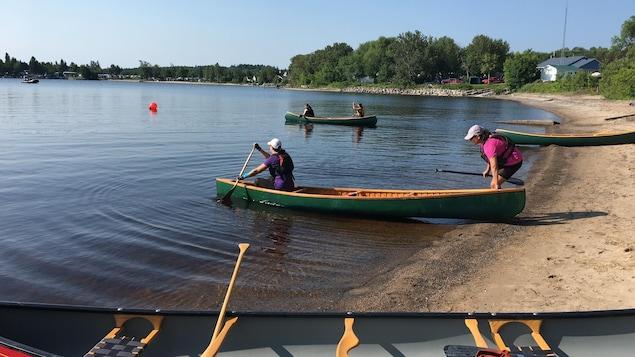 Deux femmes embarquent dans un canot.