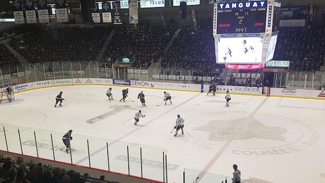 Des centaines de partisans regardent des joueurs en action sur la patinoire.