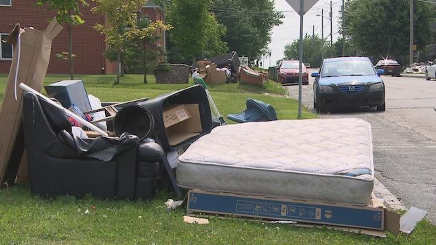 Des gros déchets comme un matelas, un divan, des grosses boîtes de carton en bordure d'une rue.