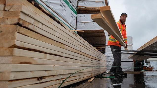 Un employé dépose deux planches de deux par quatre sur un chariot élévateur.