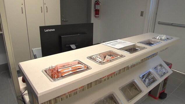 L'accueil de la salle d'injection du centre Spectre de rue, où du matériel est disponible pour les usagers, dans des bacs placés devant un poste de travail informatique.