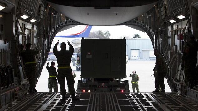 Des militaires chargent un conteneur dans un avion.