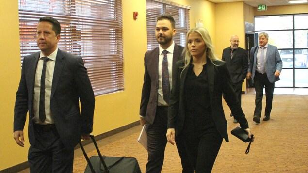 Les cinq personnes marchent dans un couloir, l'un des avocats tire une valise contenant vraisemblablement des documents.