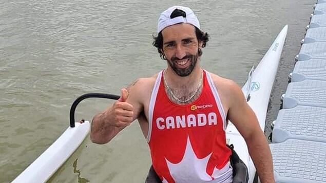 Un homme dans une embarcation le pouce en l'air souriant à la caméra.