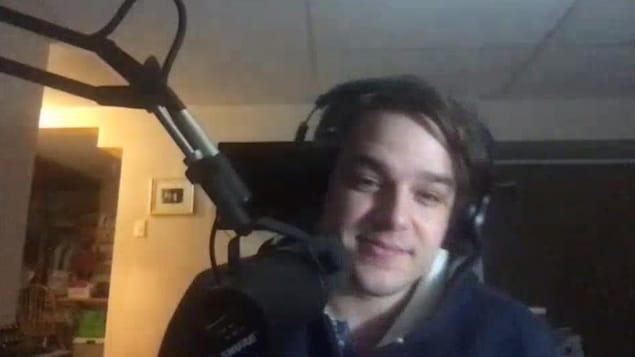 Une personne qui porte des écouteurs et parle à un micro.