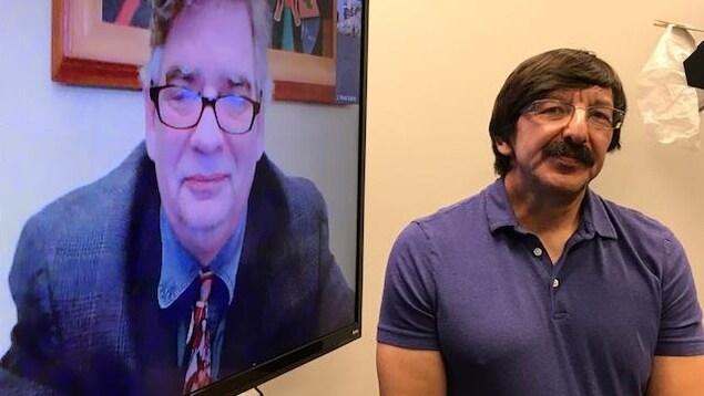 Robert Doucette à côté d'un écran de télévision avec son ami Rock Matte