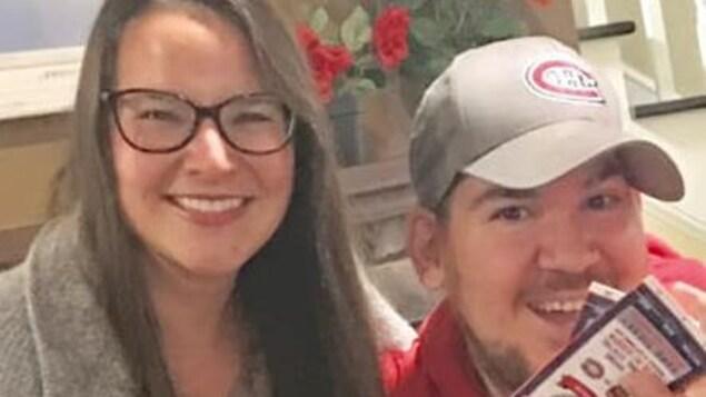 Une femme et un homme posent côte à côte montrant une paire de billets.