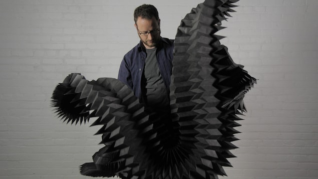 Un homme portant un t-shirt et une chemise tient dans ses mains une oeuvre d'art de plusieurs mètres de long, en papier.