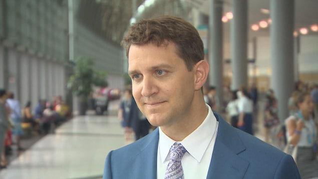 Le porte-parole national des Témoins de Jéhovah, Matthieu Rozon avec un veston bleu, une cravate violette à motifs, il a les yeux bleus, les cheveux châteaux courts.