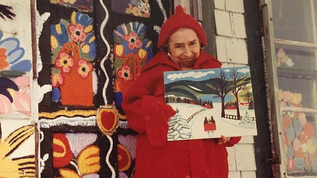 Maud Lewis debout devant sa maison, un tableau dans les mains
