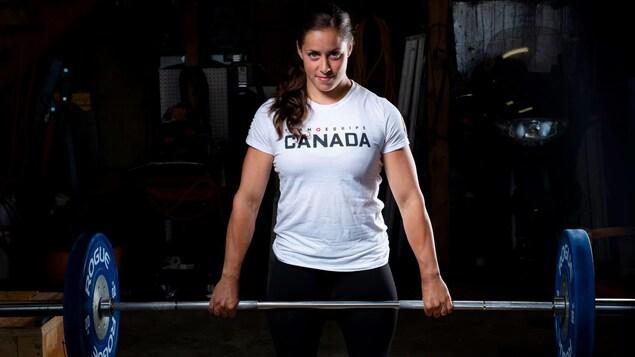 En vêtements d'entraînement, Maude Charron soulève des haltères.