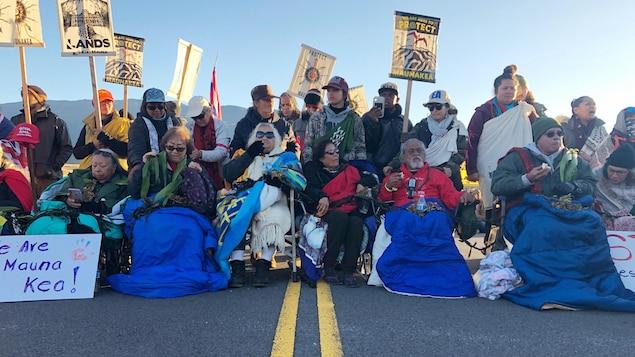 Une rangée de manifestants bloque une route d'Hawaï.