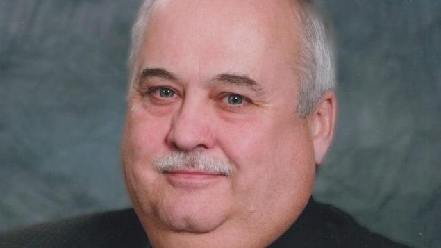 Un homme portant un veston et une cravate sourit à la caméra.