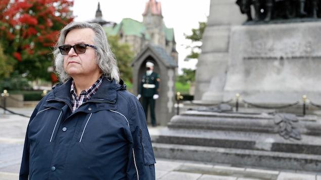 Maurice Montpetit de face avec - en arrière-plan - un militaire et le monument commémoratif de guerre.