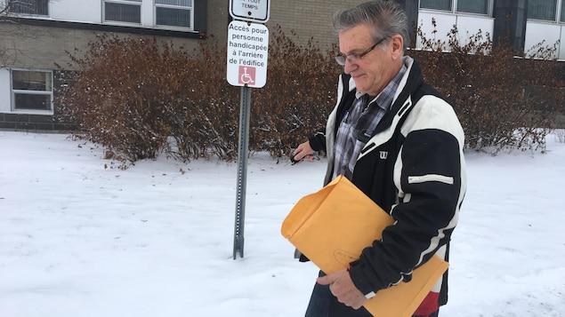 Un accusé marche vers sa voiture à la sortie du palais de justice de Rouyn-Noranda, une enveloppe jaune à la main.