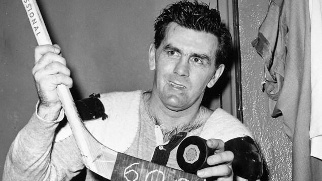 Maurice Richard montre une rondelle et son bâton de hockey en souriant, sur lequel est inscrit 600.