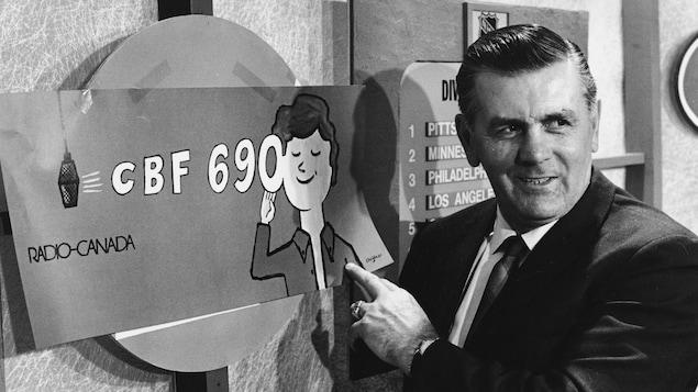 Dans un studio de radio, l'ancien joueur de hockey Maurice Richard pointe une affiche publicitaire de la station CBF 690.