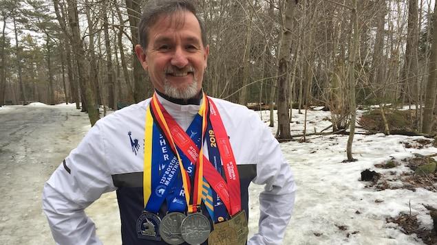 Maurice Vienneau avec cinq médailles autour du cou.