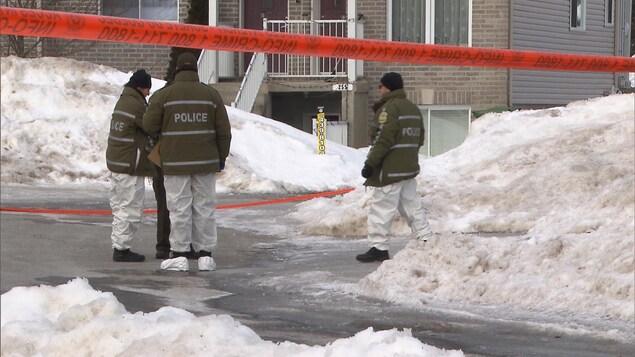 Des policiers délimitant une scène de crime devant une maison en hiver.