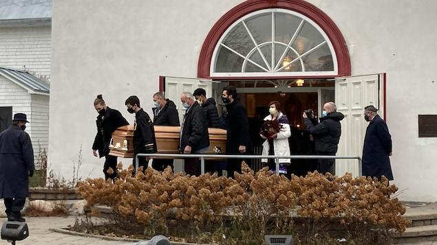 Des proches de Max Gros-Louis transportent son cercueil à la sortie des funérailles.