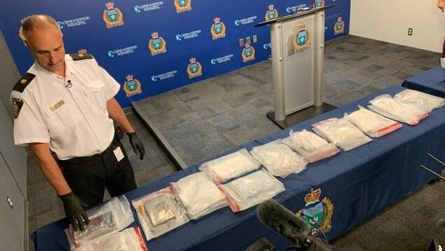 Un policier pose devant des paquets de drogue étalés sur une table au quartier général de la police.