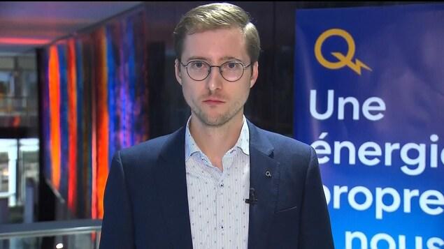 Le représentant d'Hydro-Québec regardant droit dans l'objectif de la caméra, lors d'une entrevue télévisée.