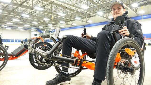 Maxime Gagnon, 25 ans, prend place sur un vélo adapté